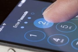 Adelaide, Australia - September 20, 2013: Entering passcode on an iPhone running iOS. iOS is the foundation of iPhone, iPad, and iPod touch. It comes with a collection of apps and useful features. The iOS 7 update features a redesigned interface and hundreds of new features.